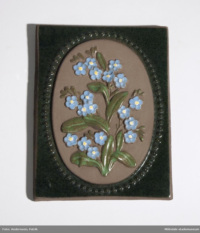"""Grön keramiktavla med Förgätmigej som motiv. Bak på tavlan är texten """"jie 908 Förgatming Dalsland"""" inristat. Tavlan är från början av 1970-talet. Formgivare var Annika Kihlman som arbetade på företaget Jie-Keramik mellan 1971-1975."""