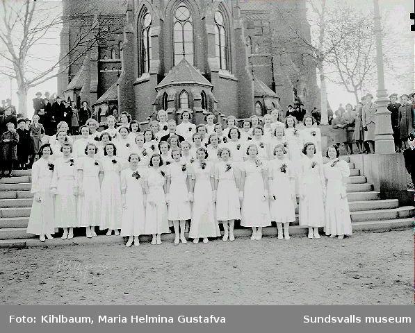 Grupporträtt framför Gustav Adolfs kyrka. Konfirmation, flickor.