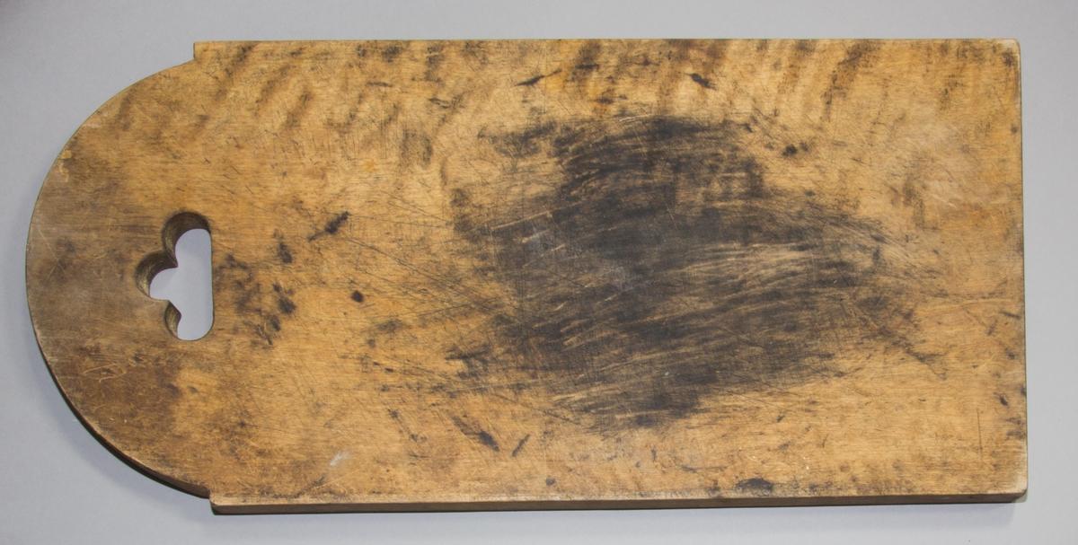 Skärbräda  tillverkad av trä. Ena kortsidan av brädan är avrundad och försedd med ett trepassliknande hål.