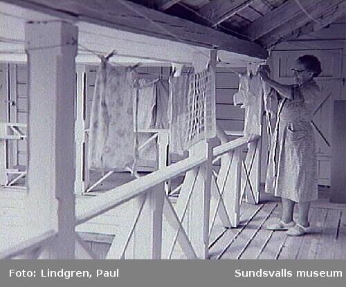 Fredsgatan 24. Kvinna hänger tvätt på torkveranda.