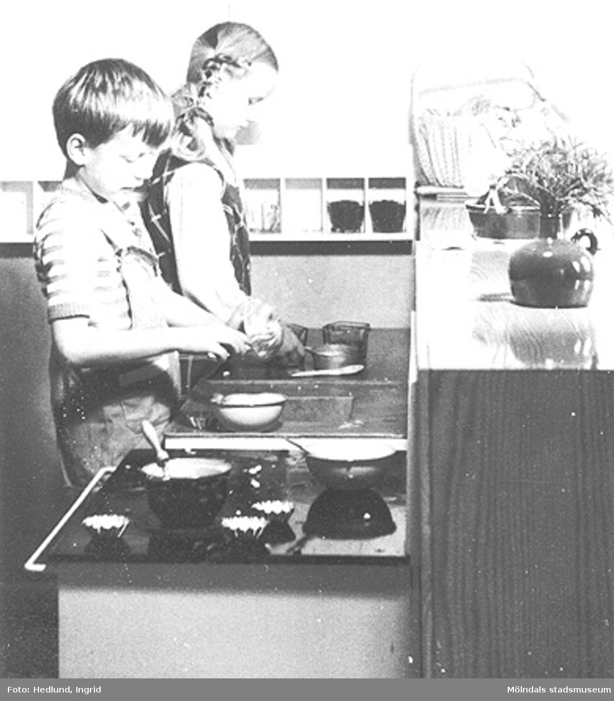 En pojke och en flicka leker att de lagar mat i ett barnkök. Daghem i Guldheden, Göteborg. Sent 1940-tal.