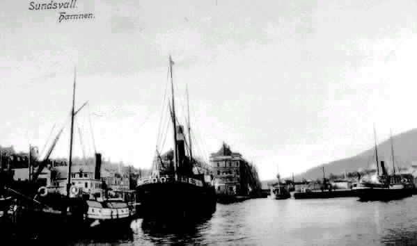 """Vy med båtar i hamnen. Bakgrund kv Skonerten och Barkassen. Båten längst till vänster möjligen """"Svartvik"""". Text på vykortet """"Sundsvall. Hamnen""""."""