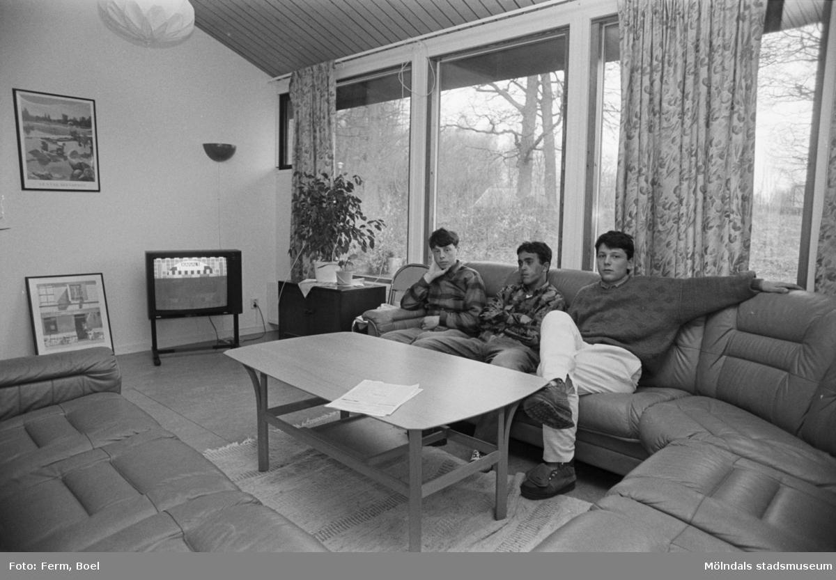 Ett allrum där tre män sitter i en soffa. Dokumentation av Sagåsens flyktingförläggning, 1992.