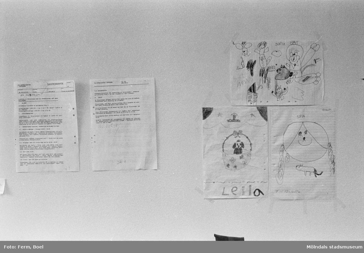 Dokumentation av Sagåsens flyktingförläggning 1992. En vägg där det till vänster sitter två maskinskrivna blad, och till höger sitter tre barnteckningar uppsatta.