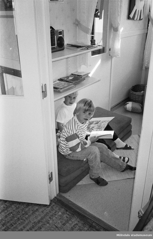 Två pojkar sitter på tre mindre madrasser i ett rum och bläddrar i var sin bok. De är fotograferade ifrån ett intilliggande rum, genom en dörr-öppning, och de sitter precis innanför. Katrinebergs daghem, 1992.