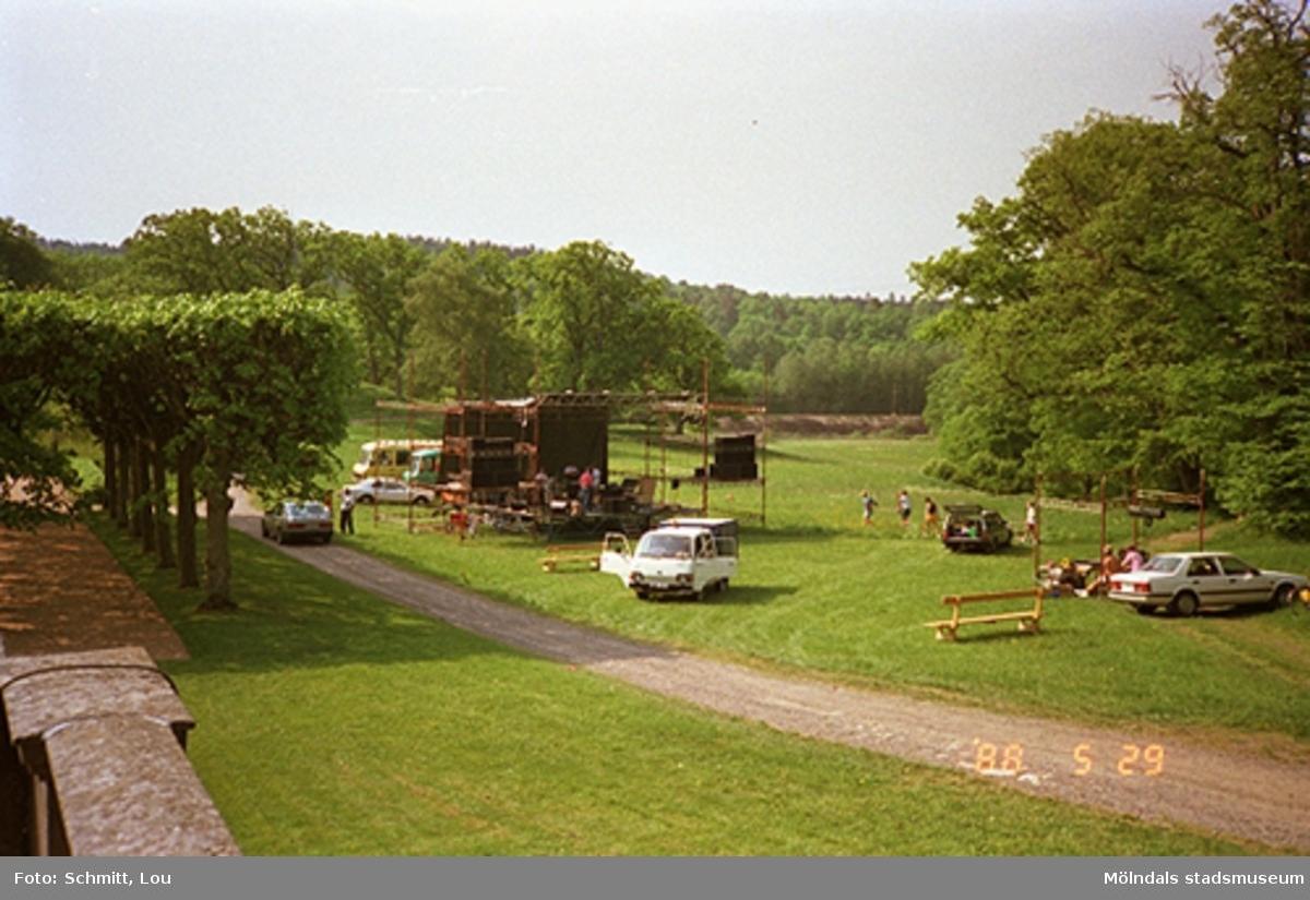 En scen håller på att byggas upp på Gunnebo slotts gräsmatta. Man ser människor som arbetar samt några parkerade bilar.
