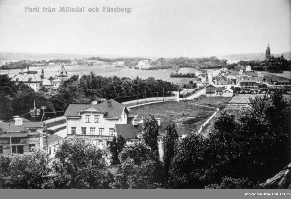"""Vykort """"Parti från Mölndal och Fässberg"""", ca 1907-1911. I förgrunden ligger området Trädgården och Kvarnbygatan som leder ned mot Mölndalsbro. I bakgrunden till vänster ser man Papyrusvillan. Uppe till höger tronar Fässbergs kyrka."""
