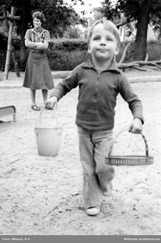 En pojke leker i sandlådan och fröken ser på i bakgrunden. Holtermanska daghemmet 1973.