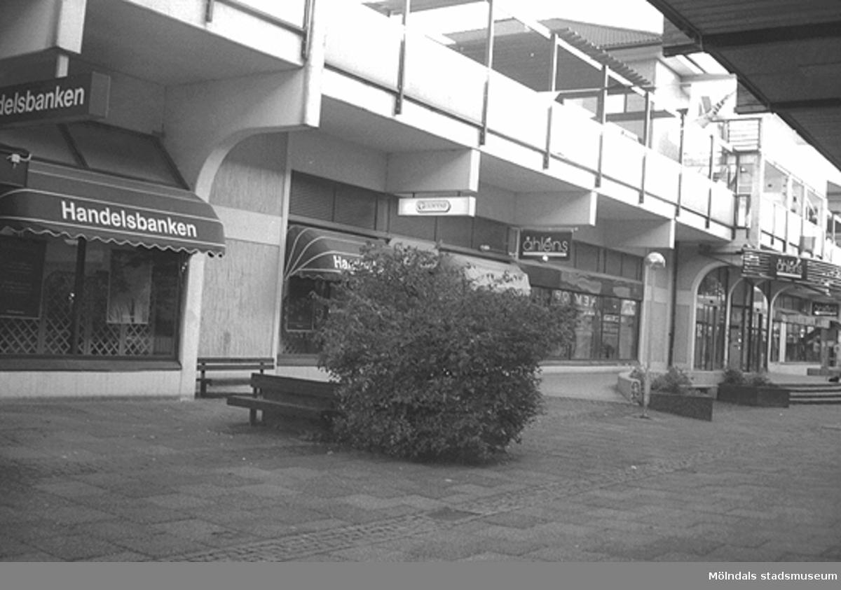 Bank och butiker utefter Brogatan. Mölndalsbro i dag - ett skolpedagogiskt dokumentationsprojekt på Mölndals museum under oktober 1996. 1996_1061-1076 är gjorda av högstadieelever från Kvarnbyskolan 9C, grupp 3. Se även 1996_0913-0940, gruppbilder på klasserna 1996_1382-1405 samt bilder från den färdiga utställningen 1996_1358-1381.