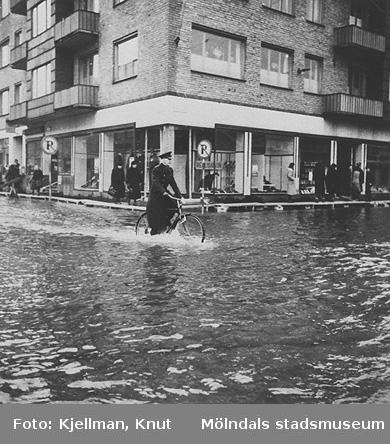 """Brandchef John Carlström cyklar över Mölndalsvägen vid en översvämning på 1950-talet. I bakgrunden ses Frändebergska huset (Frölundagatan 2 eller Göteborgsvägen 1-5). Denna del av huset kallades """"Bröderna Petterssons hörne""""."""