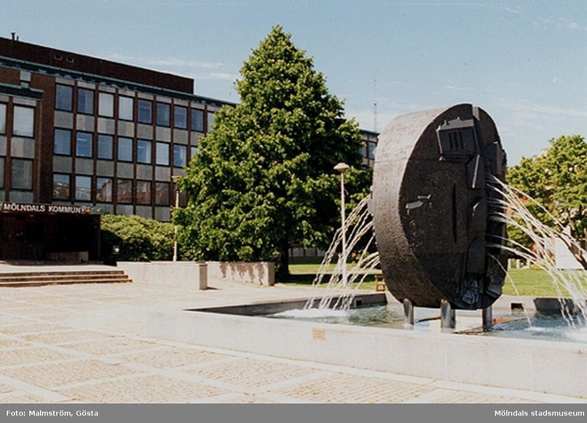 """Vy över Mölndals stadshus och torget framför, mitten av 1990-talet. Man ser Stadshusplatsen med skulptör Roland Anderssons (f. 1935) konstverk """"Faesbiaergha"""" (fontän i diabas, invigd 17 maj 1991)."""