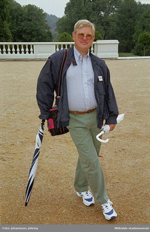 Museitekniker Alf Garthman lutar sig mot ett paraply på slottets grusplan.