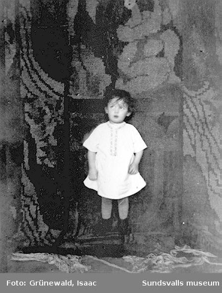 """Iván Grünewald (f. 1911) framför Sigrid Hjerténs flossamatta """"Lustgården"""" eller """"Adam och Eva i paradiset"""", troligen från 1912. Fotografiet är taget i slutet av 1912 eller början av 1913."""