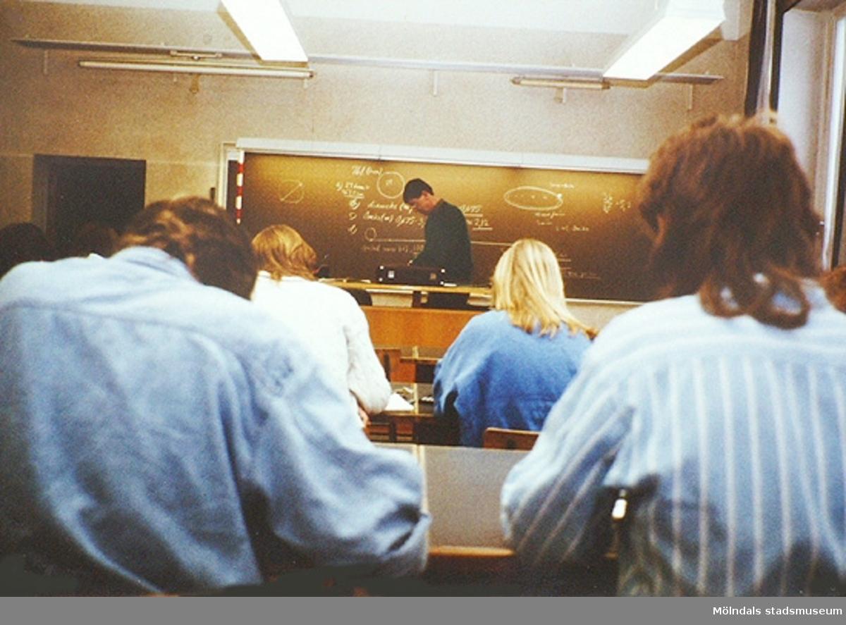 Matematiklektion där en lärare står framme vid svarta tavlan och elever sitter i bänkar.