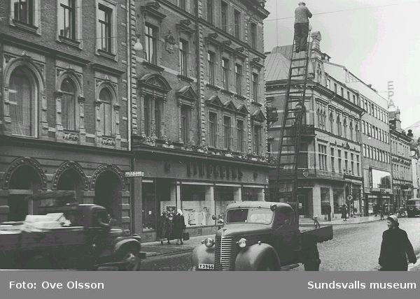 """Text: """"I upplysningens tjänst är  den här mannen, som kommit sig upp för att utbyta lampor på det att vår väg, Storgatan, ej skall bli alltför mörk att gå"""". Storgatan västerut mot Thulegatan."""