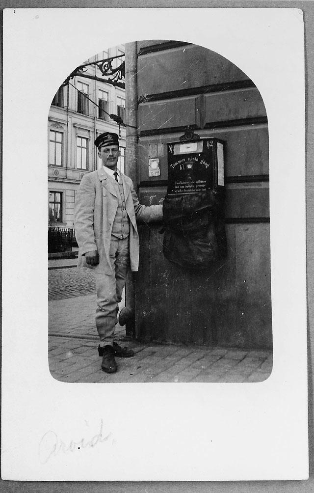Brevlådtömning - troligen vid Mosebacketorg - i Stockholm, åren 1908-1910. Brevlådtömmare är brevbäraren och biträdande postvaktmästaren vid postkontoret Stockholm 1, ankommande avdelningen Carl Arvid Palmberg.