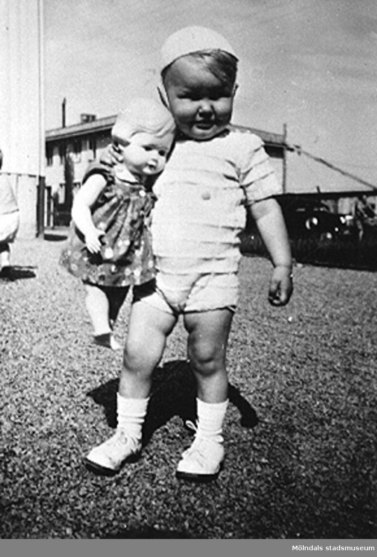 Ett barn med en docka på Krokslätts daghem, Dalhemsgatan 7 i Krokslätt. Under Margit Emilssons (gift Wannerberg -52) praktik som biträde1945-10-01 - 1946-08-01.