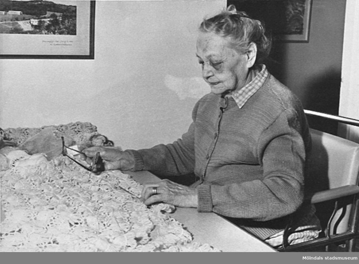 En kvinna sitter vid ett bord med garn i arbetsterapin på Lackarebäckshemmet, okänt årtal.