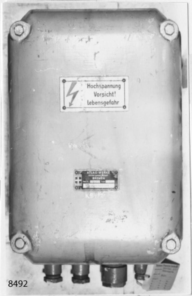 Fördelningslåda, riktare-sändare, i en kåpa av lättmetall med lock. Detta är fastsatt med fyra bultar. Kåpan försedd med öron för fastsättning samt undersidan fyra kabelintag. Gråmålad. Märkning: Hochspannung Vorsicht! Lebensgefahr. Atlas-Werke Aktiengesesellschaft Bremen. Fabr. Nr 29484. Likriktningssändare.
