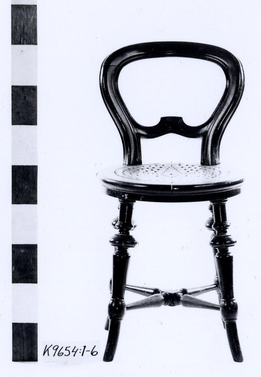 Stol av ek, svartbetsad. Svarvade ben med svarvade korslagda slåar. Rund sits med runda, perforerade hål i centrum. Bågformat ryggstöd med skuren tvärslå.
