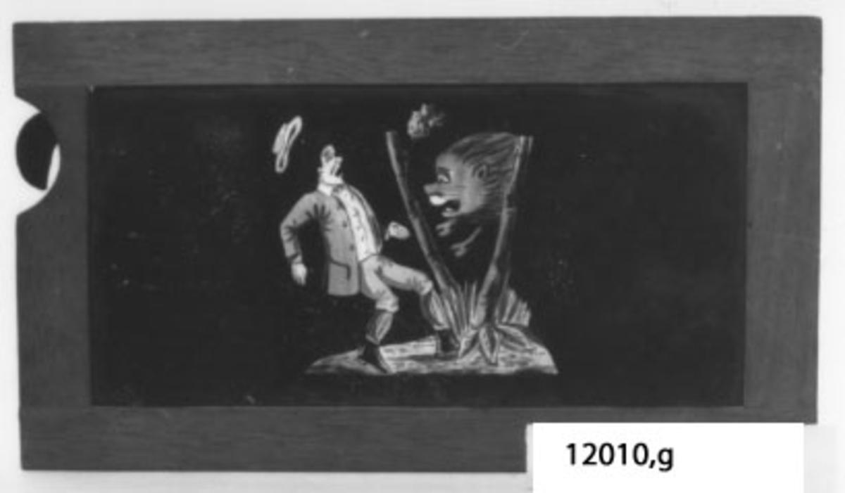 Glasbild till skioptikonappparat.målad glasskiva, Rektangulär träram med infattad glasskiva med motiv: Förskrämd man som möter ett lejon.