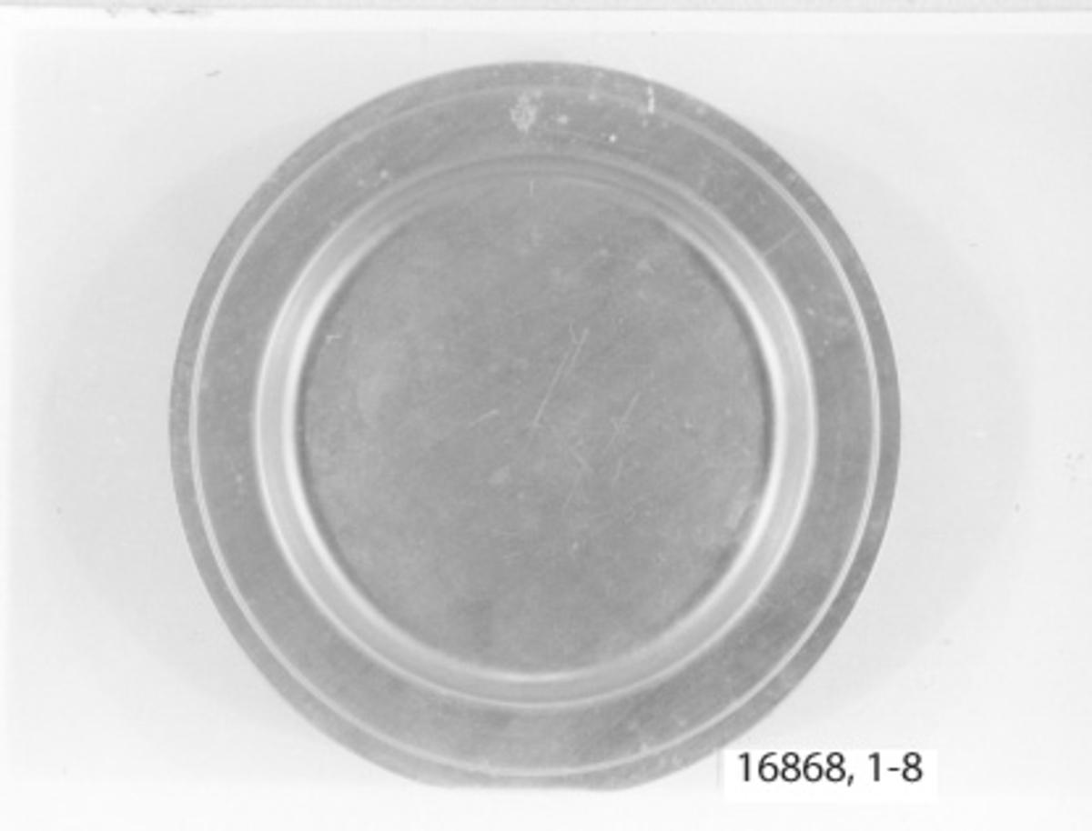 Flat tallrik av aluminium, bräm 32 mm bred, spegeln försänkt cirka 20 mm. Ytterst på bräm mindre kant 10 mm. Märkt med stämpel på bräm= krönt ankare inom tre kronor.