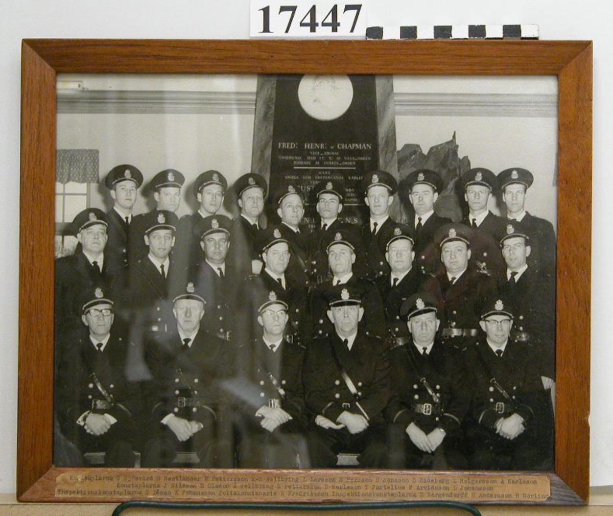"""Svartvitt fotografi inom glas och ram, föreställande gruppbild av tjugofyra män i polisuniformer, stående i modellsalen framför minnesmonumentet av F H Chapman. Ramen är av ek, B= 20 mm, nederst sitter ett gulnat papper fästat med personernas namn - se inventariebilaga. Baksida av papper med text: """"Marinens poliskår 1964"""". Neg.nr 13158. Neg.nr A 21 7:1A"""