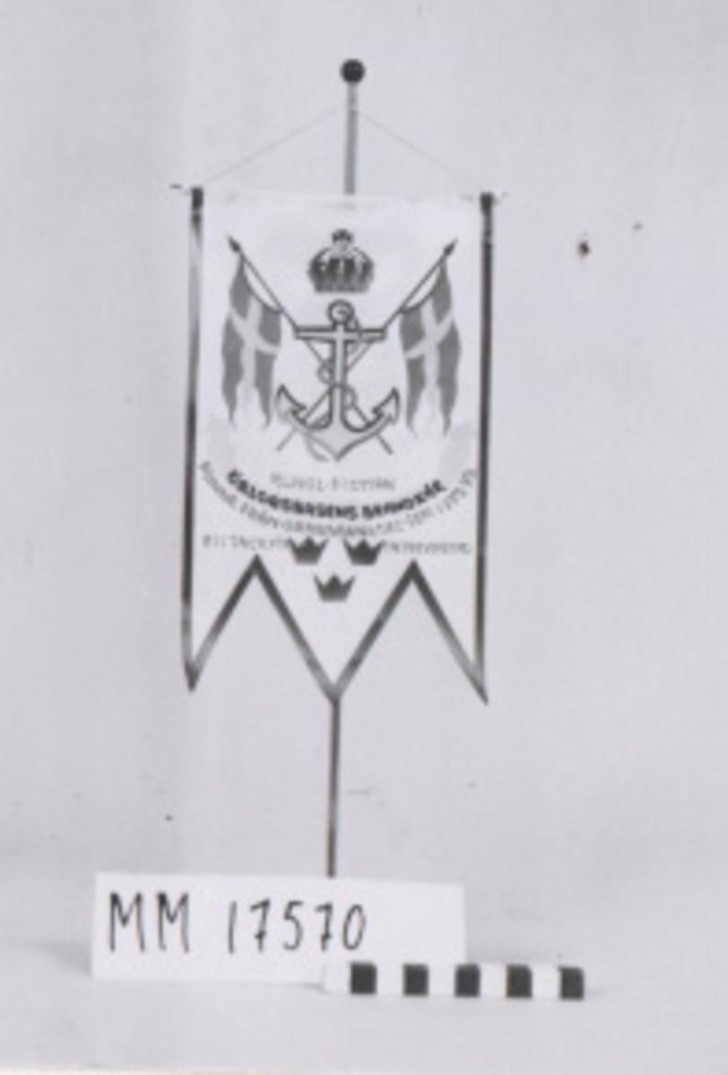 Bordsstandar bestående av tretungad flagga i vit nylon på stång av metall med plastfot. Flaggan har ensidigt tryck= krönt stockankare med två korslagda örlogsflaggor bakom. Under ankaret en banderoll och tre kronor. Handtextat: Kungl. Flottan örlogsbasens brandkår minne från grabbarna dec-sept 1072. Etttack för en trevlig tid.