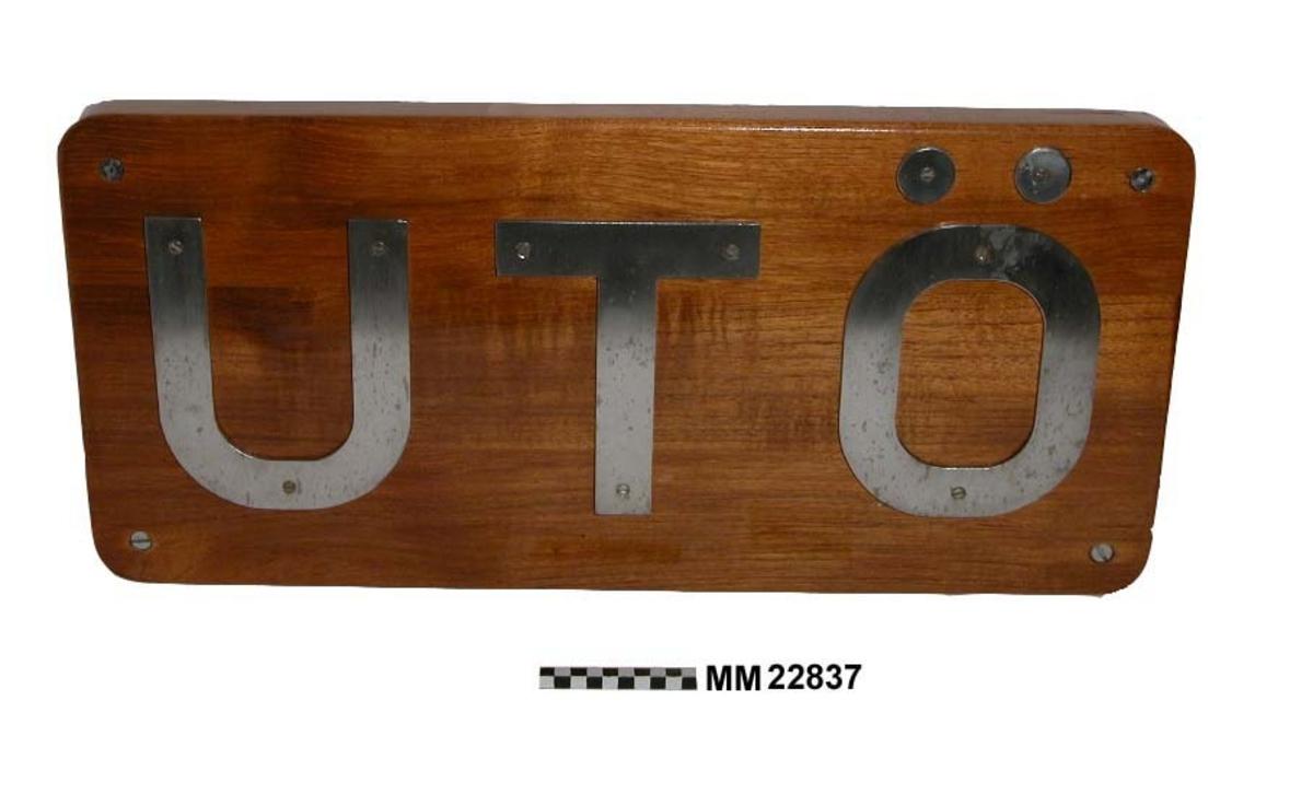 """Text: """"UTÖ"""". Bokstäverna i 4 mm tjockt stål fastskruvade på fernissad träplatta med rundade hörn. Fäste: Fyra st bultar av rostfritt stål med brickor och muttrar (En mutter saknas). Baksidan försedd med lös, fem mm tjock gummiplatta. Detta är den större av två (Se accnr 22838)."""