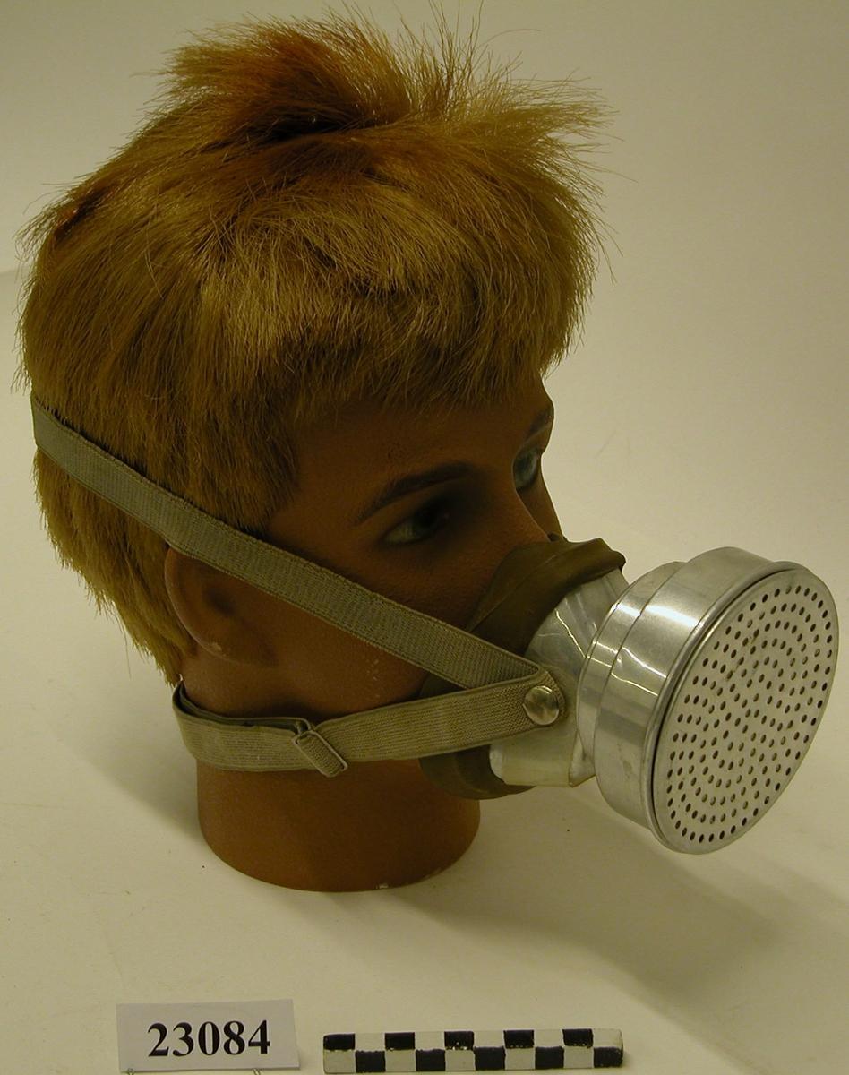 """En halvmask som täcker näsa och mun. Masken av aluminiumplåt, med en anpassning mot ansiktet i form av en cirka 30 mm bred plastkant. Framför masken är fäst en filterhållare i form av dubbla cirkelformade dosor. Den yttre dosans botten är försedd med 21 st lufthål med vardera 9 mm diameter. Filtret enkelt löstagbart, bestående av en cirkelformad plåtask med ett hundratal lufthål i botten. Inne i asken är ett pappersfilter av vitt material lagt som sammanhållna cirklar med olika diameter. Mellan asken och filtret finns ett tunt lager vadd. En 25 mm bred remsa av genomskinlig plast täcker de två utandningsventilerna och är där försedd med lufthål med 4 mm diameter. Masken fästs mot huvudet med hjälp av två resårband med metallspännen och krokar. På maskens undersida sitter en grön, oval etikett med texten """"BICAPA STOCKHOLM"""""""