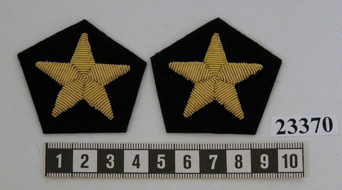 Yrkesemblem (ett par) för furir och högbåtsman vid ekonomiavdelning för underärm. Yrkesemblemet består av femkantig platta av mörkblått/svart kläde. På klädet är en femuddig stjärna broderad med guldtråd.