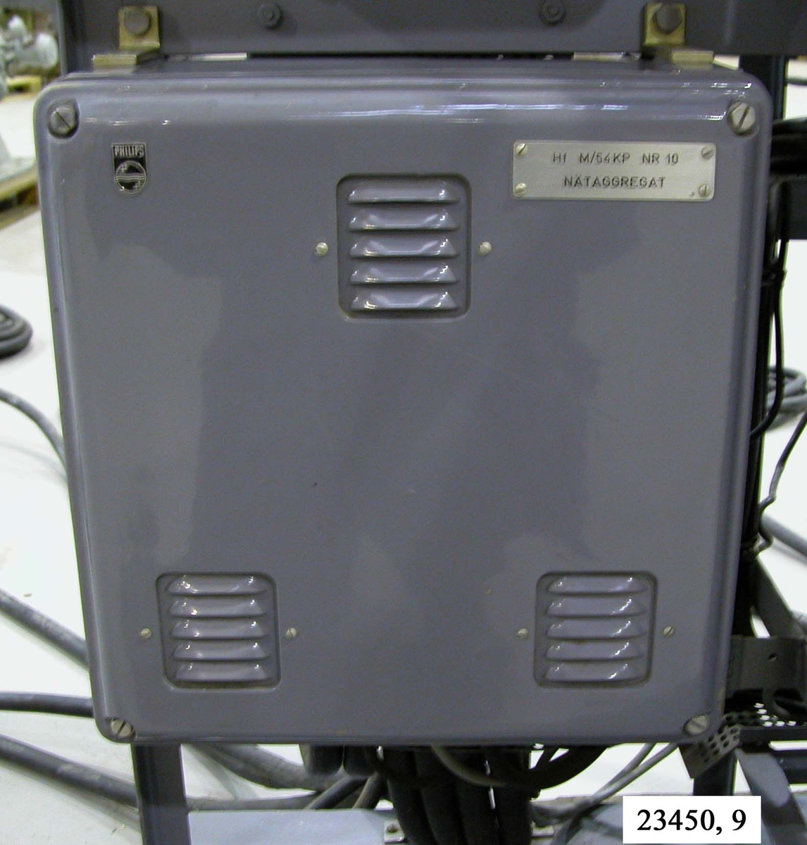 """Rektangulär, grålackerad,metallbox. I respektive hörn sitter bultar.  På boxen sitter tre stycken ventilationsspjäll. I nätaggregatets högra hörn sitter en metallbricka försedd med texten """"Hf M/54 KP NR 10, NÄTAGGREGAT"""". I relälådans underdel sitter ett antal kablar fästa. Nätaggregatet är monterat på ett hydrofonstativ, nere till vänster på stativets framsida.  Not: Kablaget ej medräknat i dimensioner."""