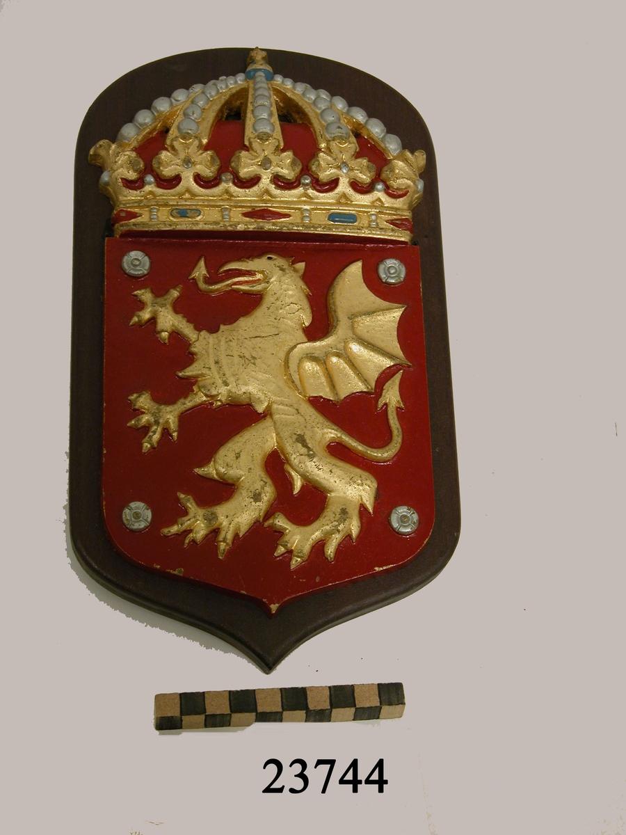 """Vapensköld, jagaren Östergötland. Krönt vapensköld av gjuten mässing monterad på brunbetsad platta av trä. I rött fält en gyllene grip med drakvinge och draksvans samt örnklor på fötterna. I vart av sköldens hörn en ros av silver. På träplattans baksida skrivet med tusch: """"Kompoff ÖGD"""" samt självhäftande lapp med text """"Vapensköld typ B Jagaren Östergötland. Nr 80:1-3""""."""