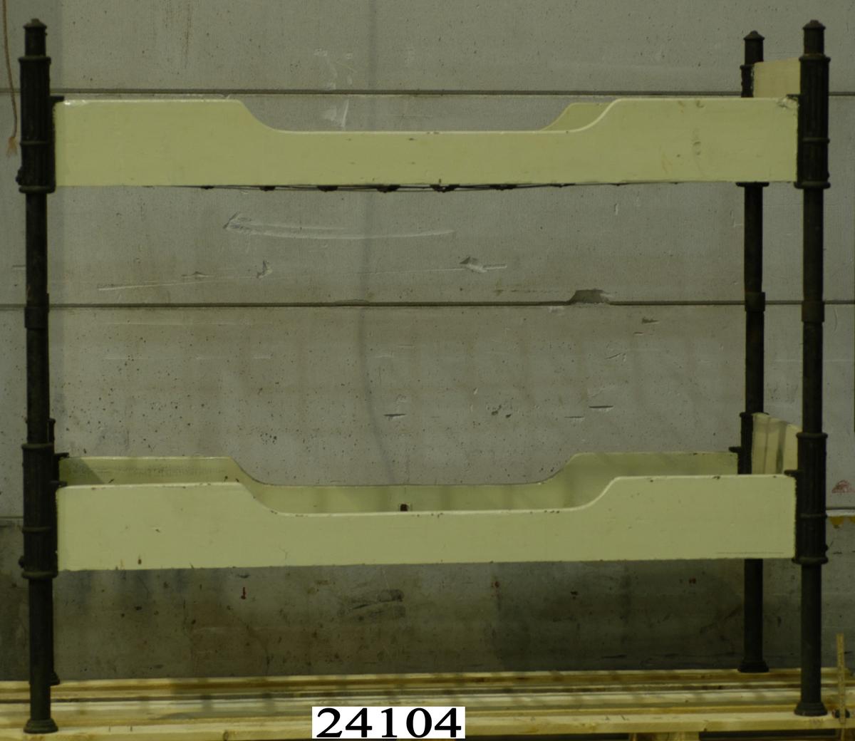 Delbar våningssäng. Grön- och svartmålad ram av gjutjärn. Lång- och kortsidor av trä, en kort och en långsida har ljusgålt målade trädelar. Gallerbottnar av metall. Kortsidorna av gjutjärn har en krona och två snedställda ankare på var sida i relief. Träsidor på en kort och en långsida ej gulmålade, dessa har sin bruna färg kvar.