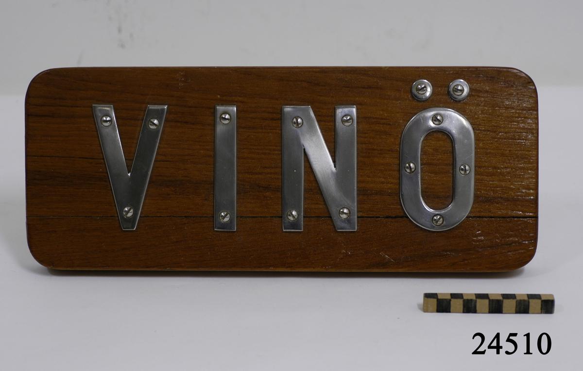 """Rektangulär, lackad träplatta med rundade hörn. På framsidan versala bokstäver av rosfritt stål """" VINÖ """" som är fastskruvade från brädans framsida. Bokstävernas höjd: 100 mm. På baksidan tre stycken hål för uppmontering samt en vit klisterlapp med text: """" MOHS, 0366 """" och streckkod. Brädan är sprucken."""