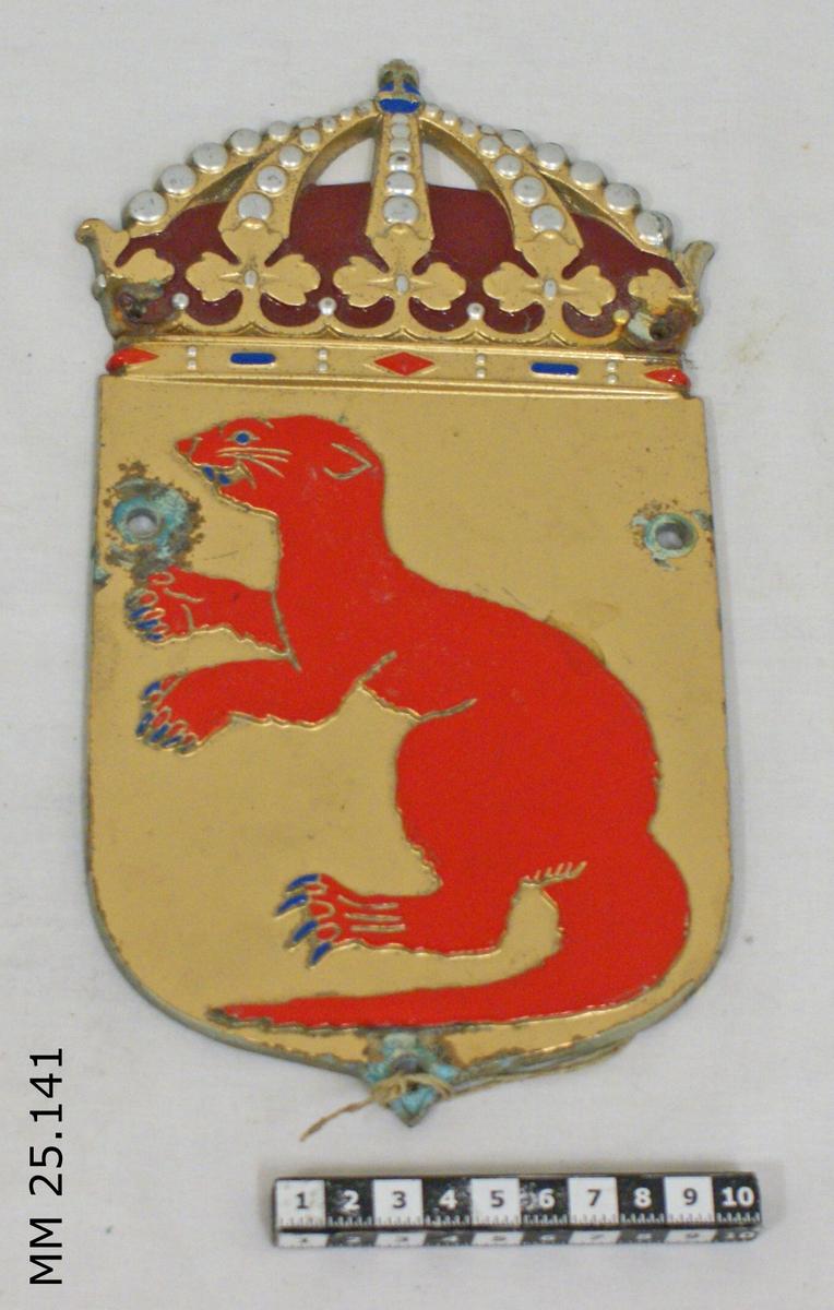 Vapensköld i metall. Överst krönt med kungakrona. På guldbotten en röd utter som på bakbenen med blå klor, huggtänder och ögon. Skölden genomborrad för upphängning på tre ställen, två över och ett under. Vid skruvhålen är färgen bortflagad.