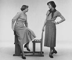 Två modeller i kjol och polotröja. Modellen till vänster sitter på en bänk feba012126356