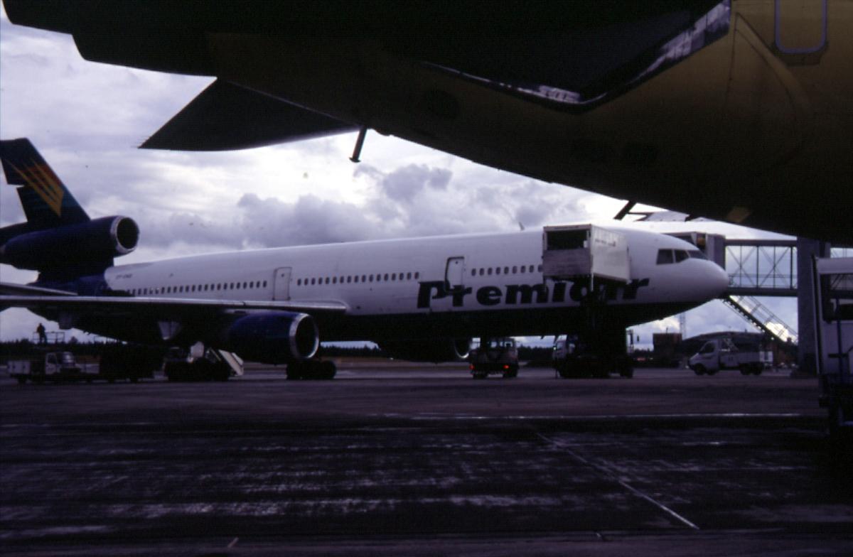 Luftfart, 1 fly på bakken ved terminalbygningen, DC-10, OY-CNS fra Premiair.  Landgangen og 4 kjøretøyer rundt flyet.  Buken til 1 annet fly i forgrunnen.