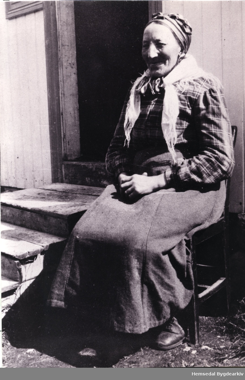 """Guri Liheim, fødd Skøyten (1873-  ) Guri vart kalla """"Store-Guri"""". Her sit ho utanfor huset sitt. Biletet er teke i tidsrommet 1940 - 1950."""