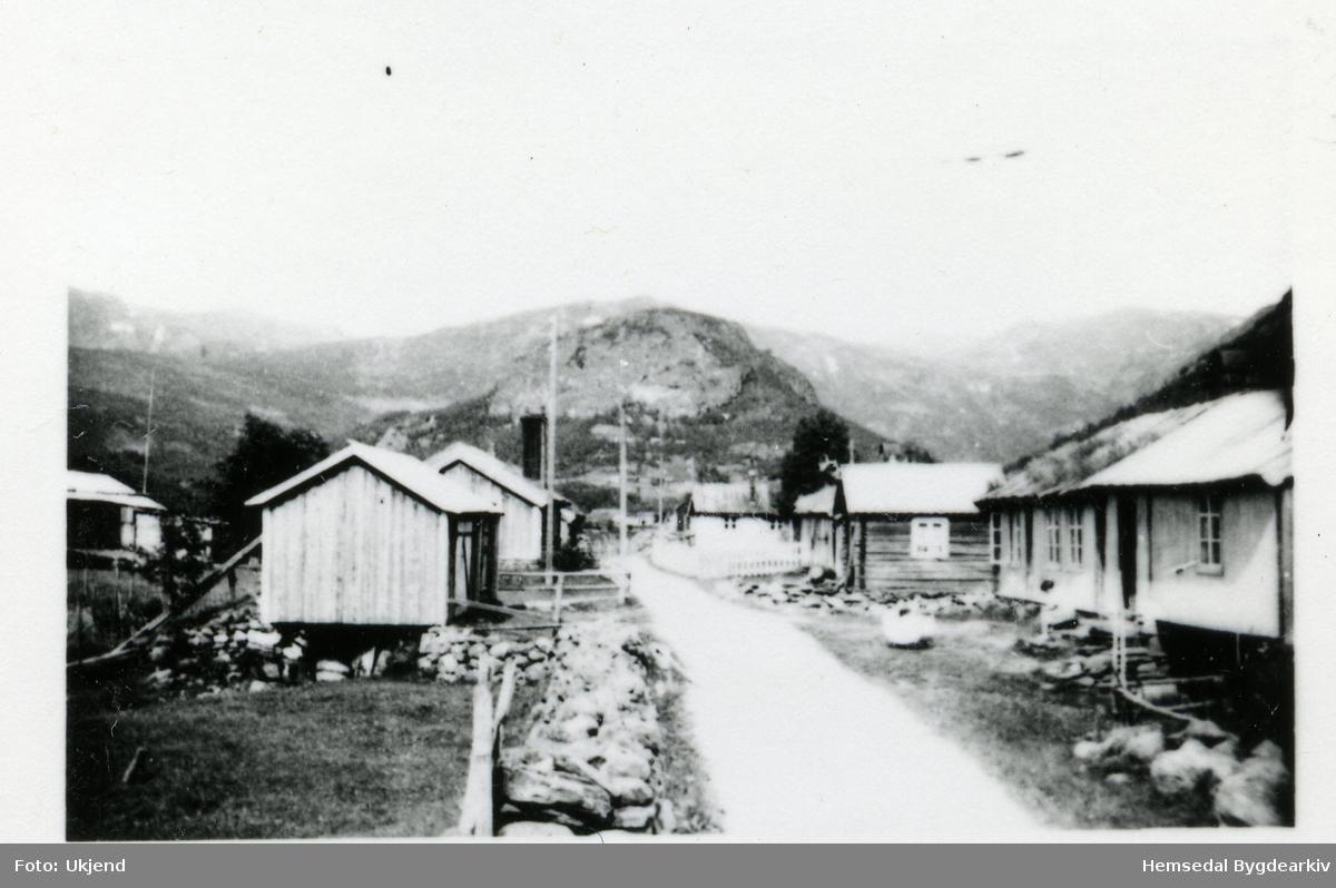 """Moahuset. Her var det 11 hus med stort og smått.  I huset til høgre hadde Per Træe """"butikk""""- Perstova (Persstugu, dialekt). Han tok mot varer frå bøndene og reiste nedover og selde. Så tok han med seg byvarer heim att. Grøndalsvegen og Hallenuten bak. Fotografiet er frå kring 1925."""