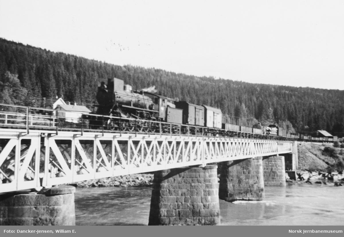 Brua over Lågen med Langsveen med passerende godstog trukket av damplokomotiv type 26a