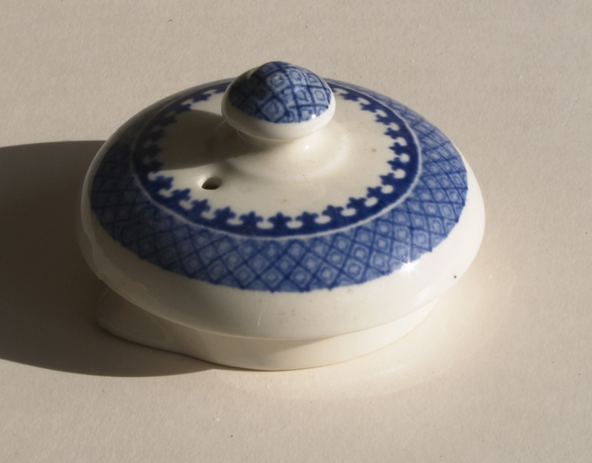 Laget av porselen, som er brent, malt og glassert. Hvit bunn med blått mønster. Selve lokket er rundt og har en form for tut/skjenke punkt. Hull i lokket, til å binde en tråd rundt knappen på toppen.