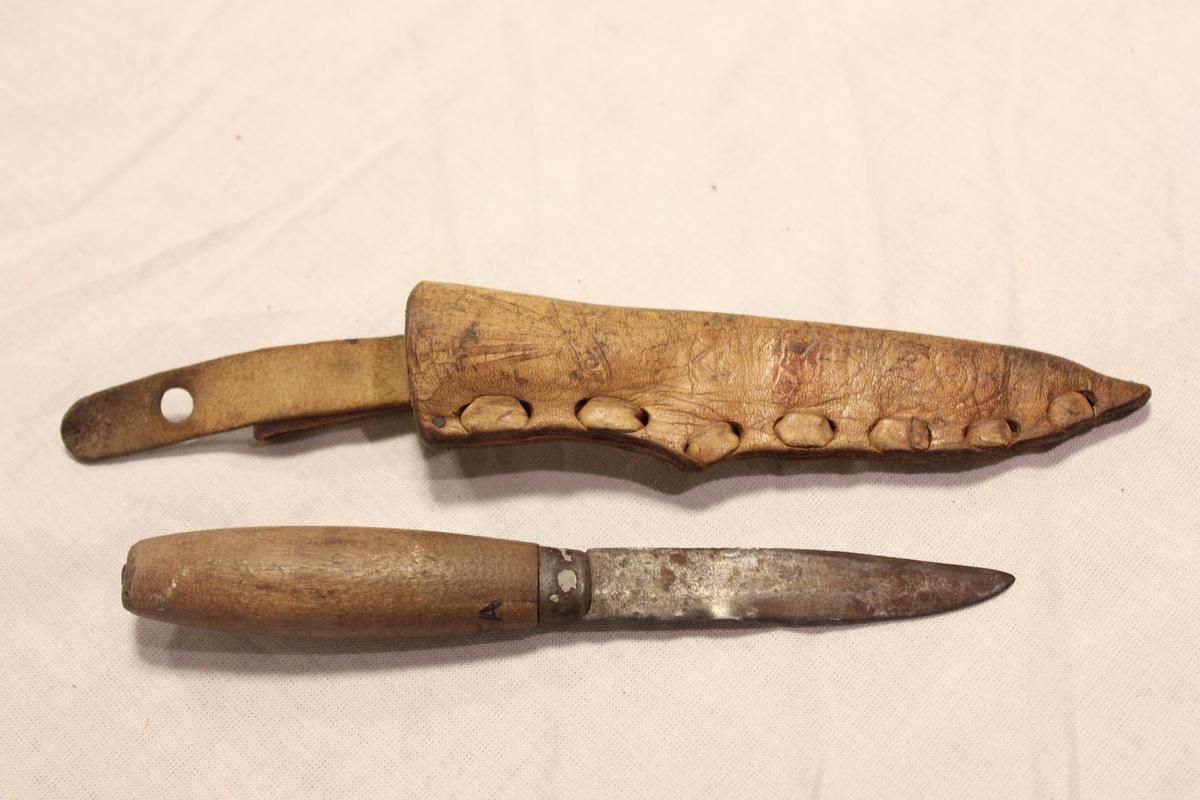 Lærslire til å sette kniven i. Laget av lær og har en gul/brun farge. Den er sydd sammen av en tykk lærtråd og har øverst to hemper som er festet med en skrue. Selve sliren er formet som et spisst knivblad.