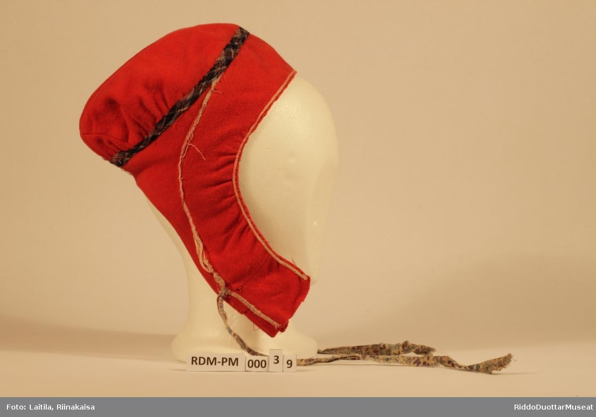 Luens hovedfarge er rød, og stoffet er av ullklede. Luen er sydd etter hodets form. Muodusbirasbáddi er et hvitt pyntebånd , 2 mm bred.  På den venstre muodusbirasbáddi ser man at der har vært en blå søm/blå ptyntebånd av no slag.  Speallevearka er et hvitt, heklet bånd rundt kanten mot ansiktet på kvinnelue, 2 mm bred.   Ravda er et 1 cm bredt bånd som er av blåe nyanser, og rødt og hvitt, et slags rutemønster.. Gahperbáttit er bomullsbånd med lilla og blå blomstermønster, hovedfargen var engang hvitt ser det ut som, 30 cm lang. Innvendig er luen foret med et rutet mønster bånd som er 5 cm bredt.