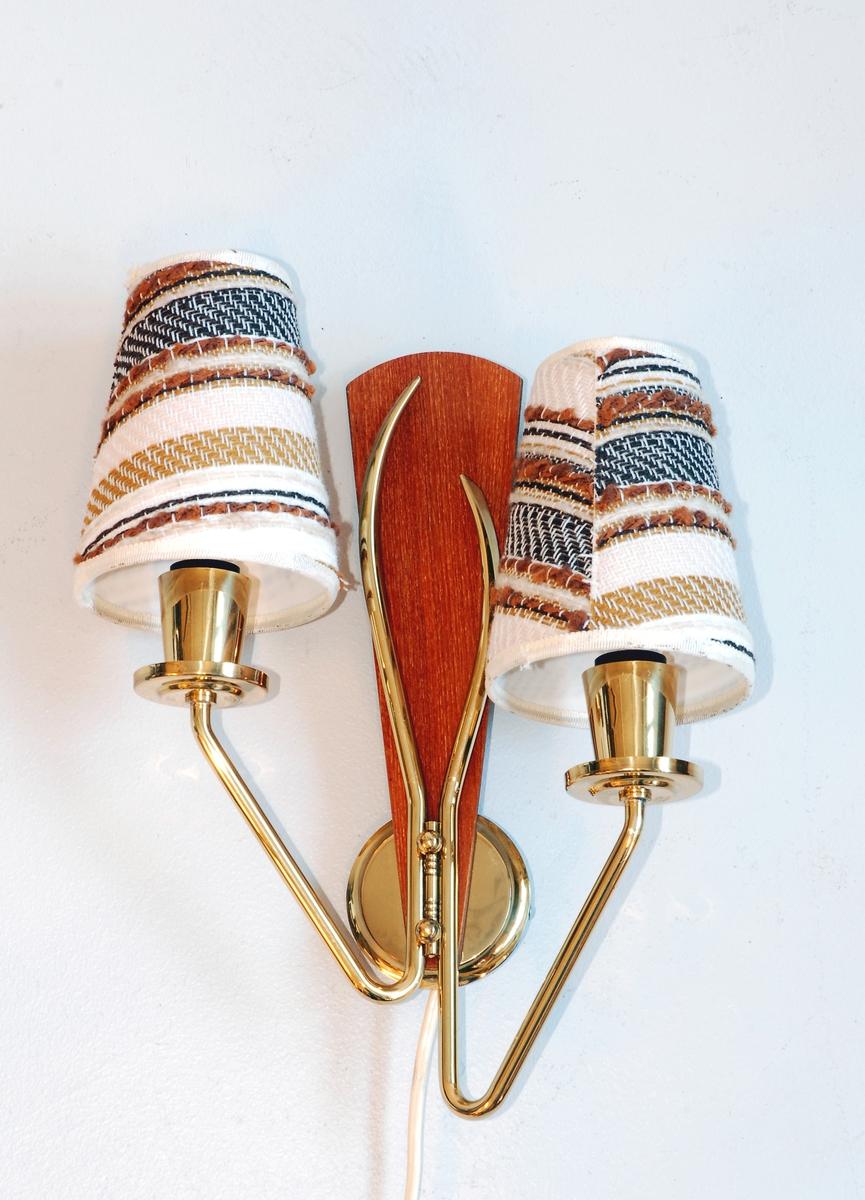 To-arma lampett - messingfarga armar montert på vifteforma teakplate. Tekstil skjermar.
