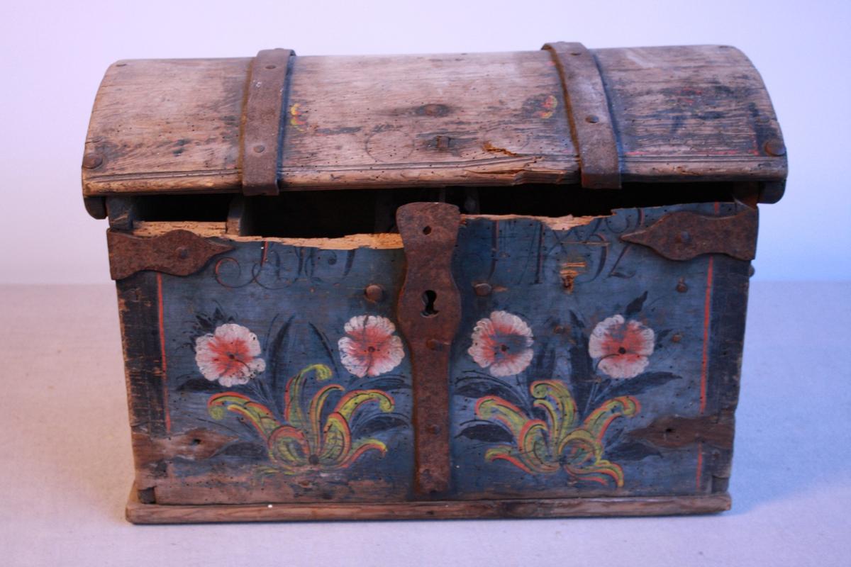 Svært slitt øydelagt kiste. Bua lok. Jernhank på begge sider. Jernbeslag over lås lok og hjørner. Jerbeslag på hjørna nede på hjørna manglar. Blåmålt med svart rand langs hjørna, dekorert med blomster. Leddik med lok, lok på leddig har løsna. Lås er øydelagt. Øvste del av framsida er brote av. Truleg p.g.a. mott. Maling slitt spesielt på lok.