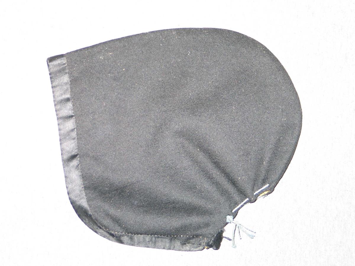 Form: Kjølform Laga av 2 like stykke. Svart klede. Kanta framme med silkeband. Fôr av sterk gult voksa(?) bomullslerret.  Ei lys blå  tvinna snor er tredd gjennom hol i nakkesplitten.  Krok og malje nedst i nakkesplitten. To silkeband for knyting under haka.