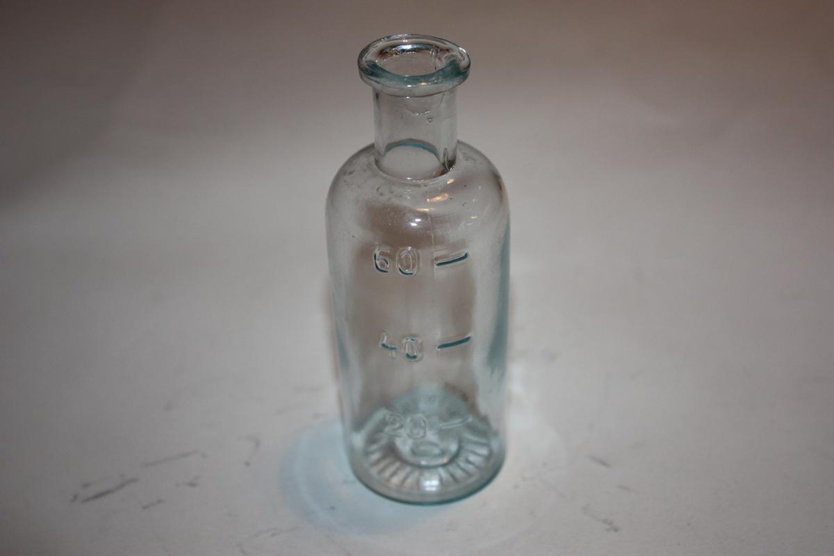Sylindrisk flaske med avrunda skulder, rett hals, utkraga munning. Krage på tuten og doseringsmål på sida