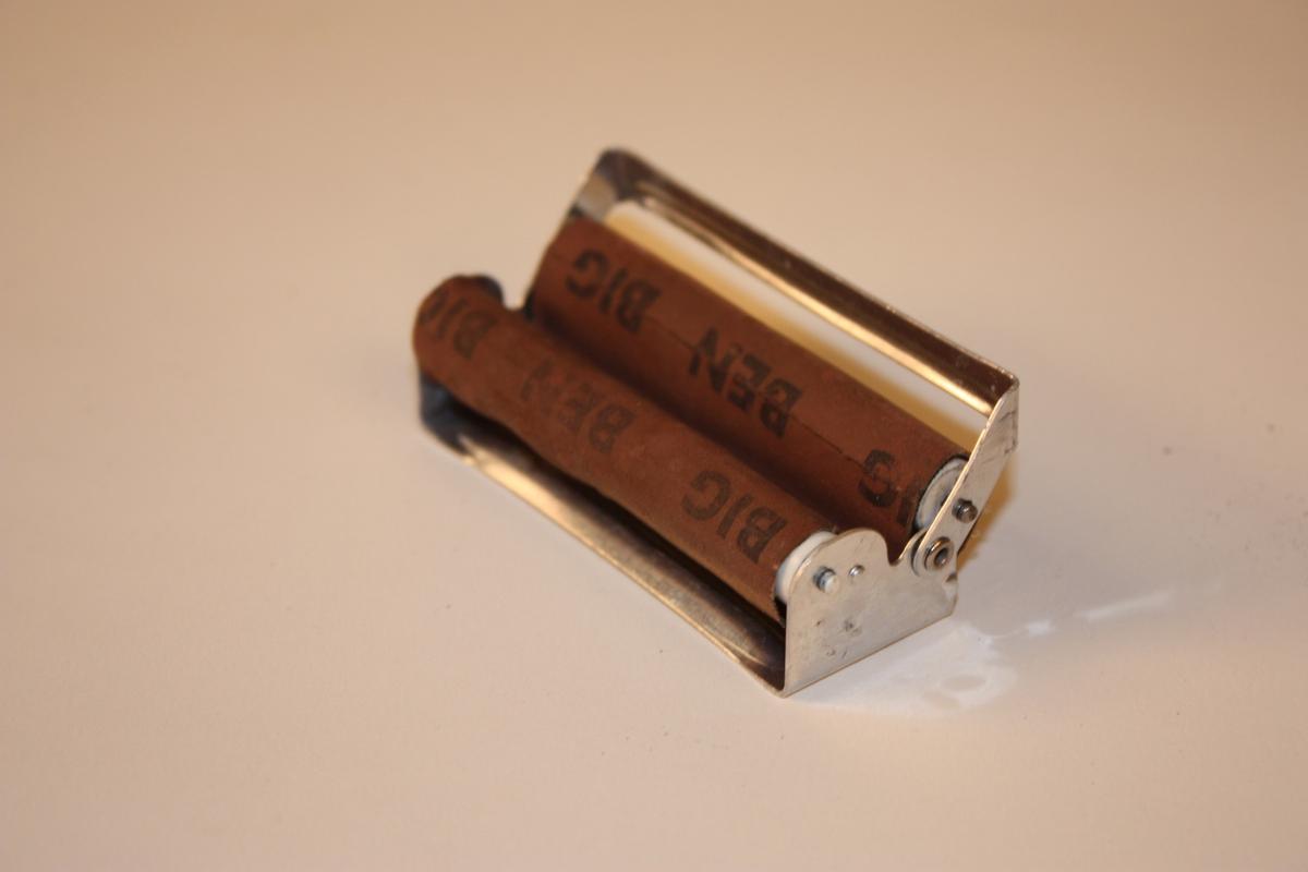Aluminiumshaldar med to plastrullar som det går eit lerrettsband rundt. Ved å legge tobakk og sigarettpapir opp i bandet kan ein på enkelt vis lage ein sigarett