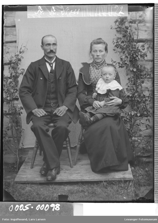 Gruppebilde av mann og kvinne med et spedbarn sittende på fanget.